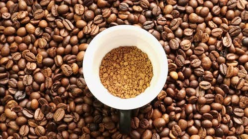 Granulated Coffee On The Background Of Coffee Greens