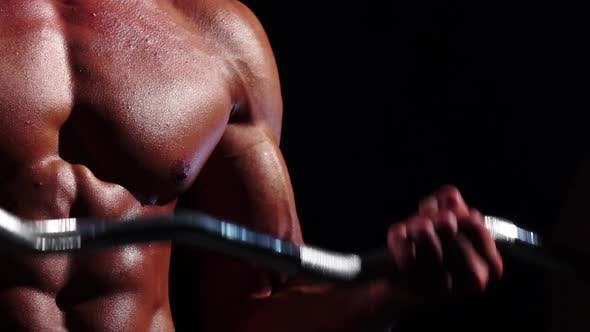 Thumbnail for Close Up Bodybuilder Training Biceps with a Barbell. Black Background. Slow Motion