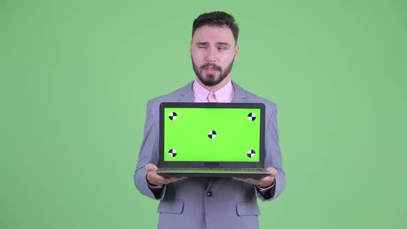 Thumbnail for Happy Young Bearded Businessman Thinking While Showing Laptop
