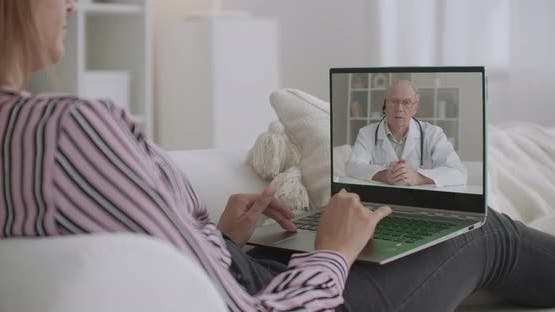 Elderly Doctor Is Lecturing Online for Patients, Young Woman Is Viewing Video By Laptop at Home
