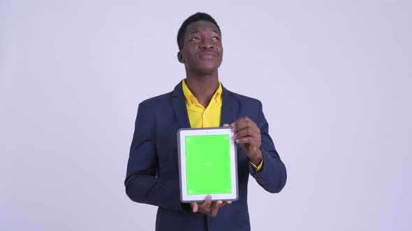 Thumbnail for Young Happy African Businessman Thinking While Showing Digital Tablet