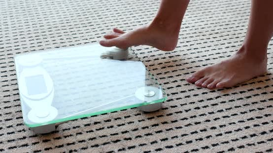 Thumbnail for Female measuring weight on health scale