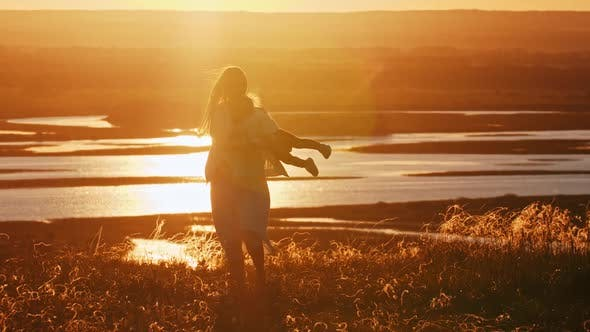 Cover Image for Young Woman with Her Daughter Playing on the Hill at Sunset