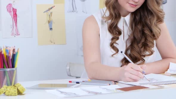 Thumbnail for Designer Draws Sketches, on the Table Sketches and Outline of the Fashion Collection