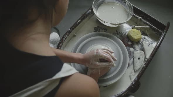 Thumbnail for Asian potter works with potter's wheel in studio