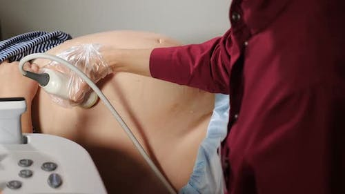 Doctor Hand Moving Transducer on Abdomen Belly Spreaded with Gel. Doctor Making Ultrasound, Sonogram