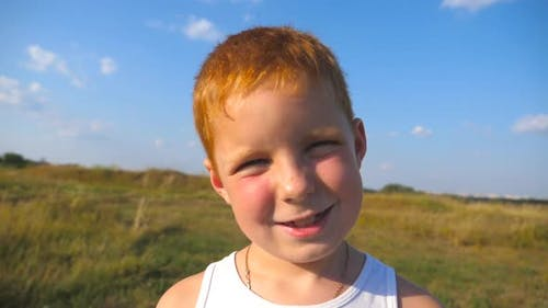 Portrait of Happy Red Hair Boy with Freckles Laughs Outdoor