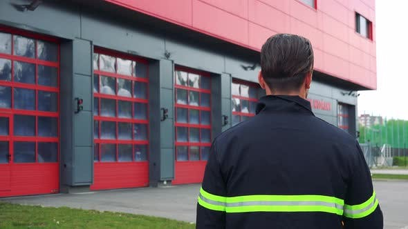 Thumbnail for A Firefighter (The Back To the Camera) Looks at a Fire Station and Puts on a Helmet