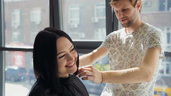 A Woman in a Hairdressing Salon Waiting To See the Results Looking in a Mirror, Smiling and Talking