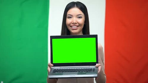 Female Holding Laptop With Green Screen, Italian Flag on Background, Emigration