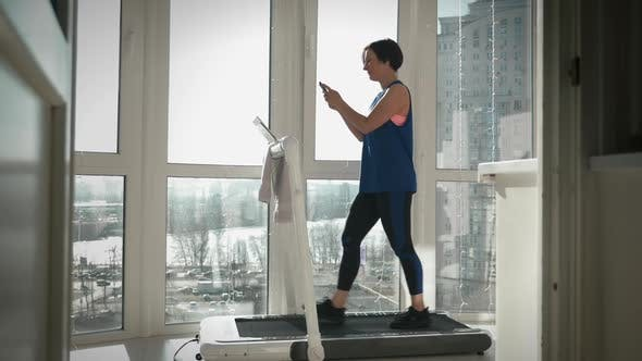 Treadmill. Fitness activity at home. Running on home smart trainer