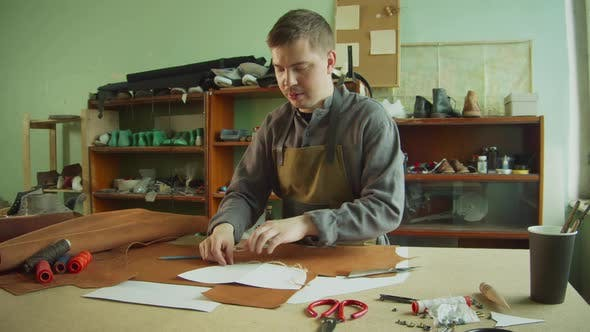 An Experienced Male Tanner Makes a Layout of Bag Elements on a Large Piece of Brown Leather on a