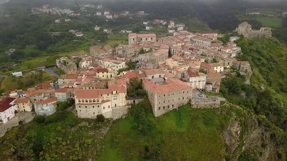 Cover Image for Aerial View Drone Flies Over Medieval Village on Hill Overlooking Misty Mountain Gorge. Cloudy Day