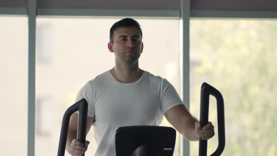 Thumbnail for Portrait of Man Training on Elliptical Trainer at Gym, Slow Motion