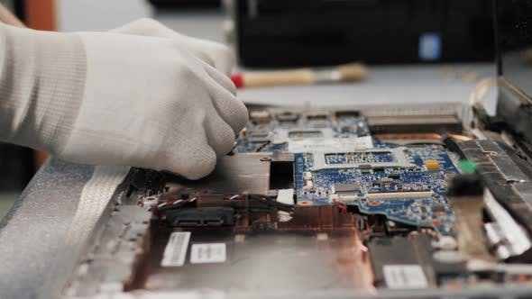 Thumbnail for Closeup Shot of Male Hands Working on Disassembling and Cleaning Circuit Board in Laptop Using Brush