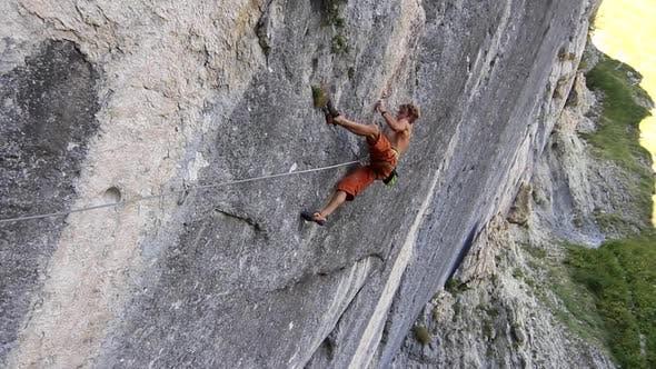 Thumbnail for A man rock climbing up a mountain.