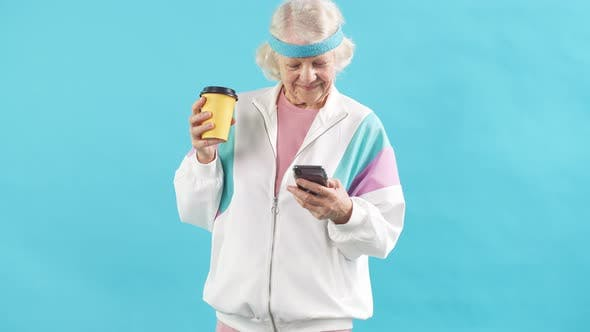 Grey Haired Mature Woman in Headband and White Sports Jacket, Has Coffee Break