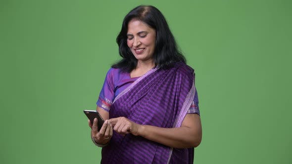 Cover Image for Mature Happy Beautiful Indian Woman Using Phone