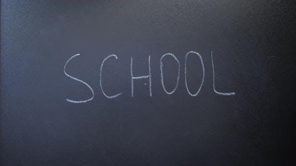 Word school written on chalkboard. Teacher writing word school with white chalk on blackboard