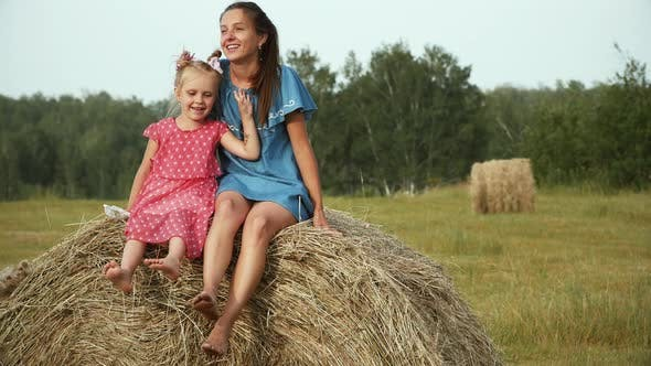 Thumbnail for Beautiful woman and five years old child sitting on haystack