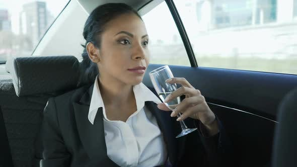 Thumbnail for Mixed Businesswoman Sitting on Back Seat of Car with Champagne, Celebration