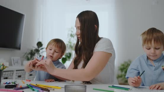 Thumbnail for A Young Mother with Two Children Sitting at a White Table Draws Colored Pencils on Paper