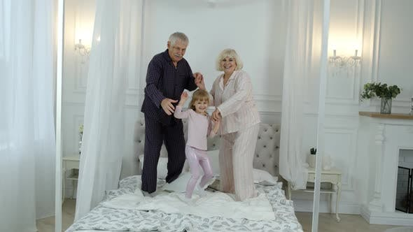 Thumbnail for Active Senior Grandparents Couple in Pajamas Jumping with Granddaughter Child Girl on Bed at Home