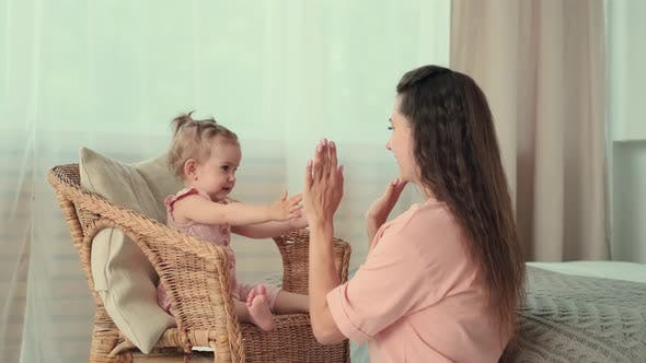 Mom Plays with Her Baby Clapping Her Hands at Home