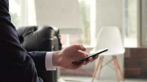 Businessman scrolling on smartphone at office, blank nameplate template for text.