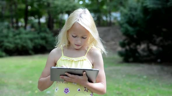 Thumbnail for Little Cute Girl Does Something on the Tablet in the Park