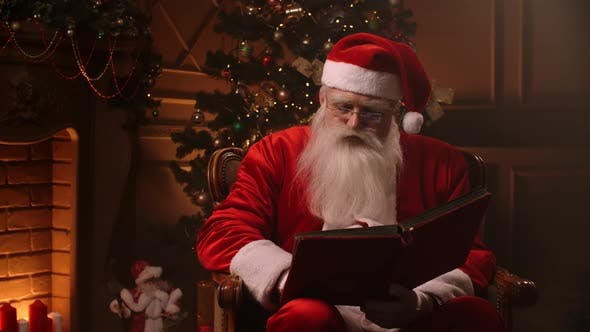 Thumbnail for Bearded Senior Man in Santa Clause Outfit Flipping Through Pages of Book with Red Cover in