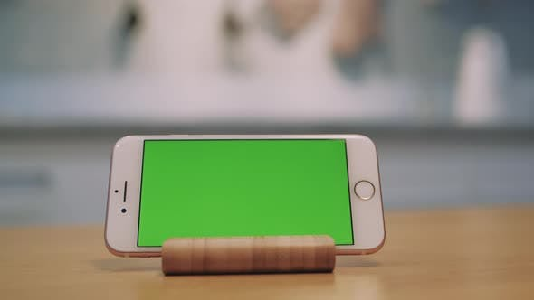 Mobile Phone with Green Screen Is Standing on the Table