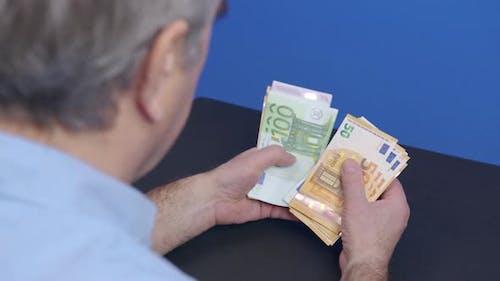 Eine Person, die Euro-Banknoten zählt Geldgeld-Bargeld-Berechnung der Europäischen Union