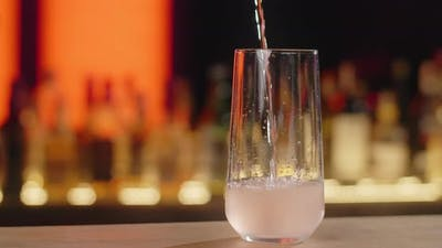 Barman Pours Transparent Sparkling Beverage to the Cocktail Glass in Slow Motion Making the Cocktail