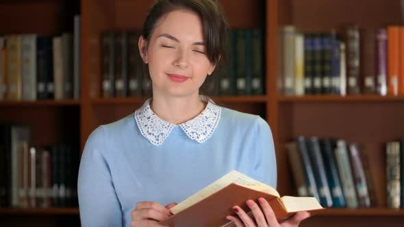 Thumbnail for Portrait of Smiling Beautiful Pretty Woman with Book in Library Office Bookshelf Background