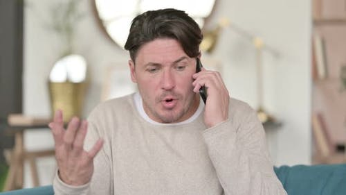 Angry Middle Aged Man Talking on Smartphone
