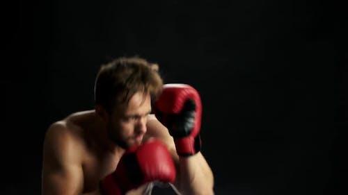 Hübscher Kämpfer in roten Handschuhen ist Boxen.