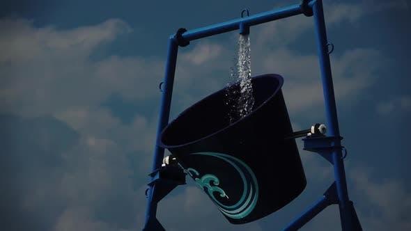 Thumbnail for Wasserpark ein Eimer Wasser dreht sich um. Zeitlupe. Nahaufnahme