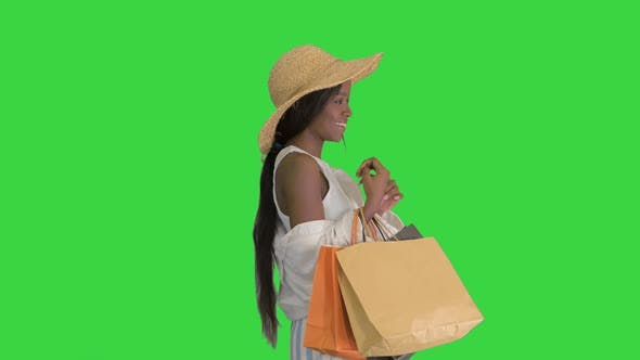 Thumbnail for Smiling African American Woman in Straw Hat Posing with Shopping Bags on a Green Screen, Chroma Key
