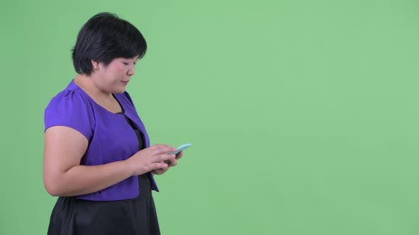 Thumbnail for Happy Young Overweight Asian Woman Waiting While Using Phone