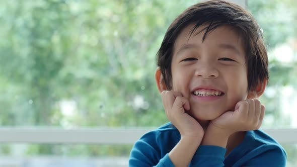 Cute Asian Child Resting Chins On Hands On Wood Table