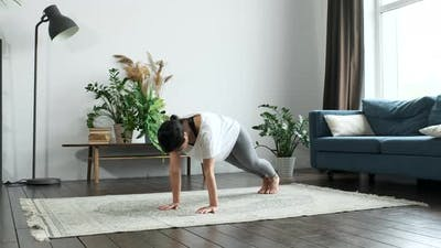 Beautiful young woman in sportswear doing plank exercises on a yoga at home