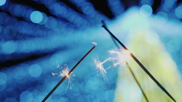 Thumbnail for Several Sparklers Burn on Blurry Bokeh of Christmas Tree
