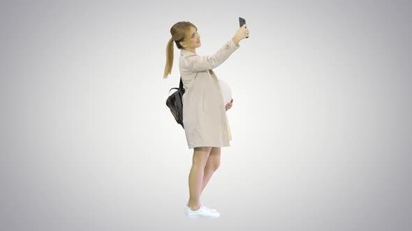 Thumbnail for Glückliche junge schwangere Frau nehmen Selfie auf Gradient Hintergrund