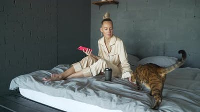 Woman in Bed Plays with Cat