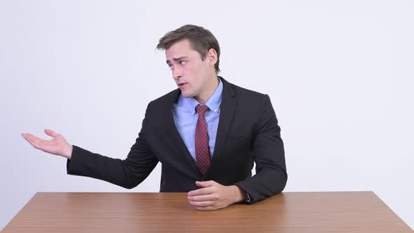 Cover Image for Young Handsome Businessman Presenting Something Against Wooden Table