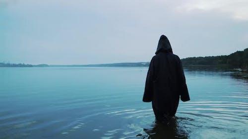 Weibliche Figur in einem schwarzen Gewand tritt ins Wasser ein. Halloween Kostüm