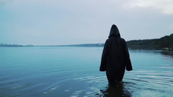 Female figure in a black robe enters the water. Halloween costume