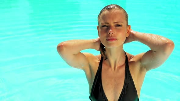 Thumbnail for Gorgeous Woman Brushing Her Hair Up with Two Hands While in the Pool