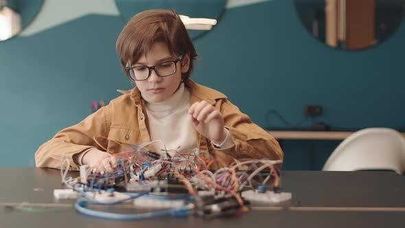 Portrait of School Kid Constructing Robot